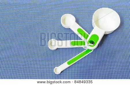 Set Of Measuring Spoon With Green Handle Placed On Blue Scotch Background
