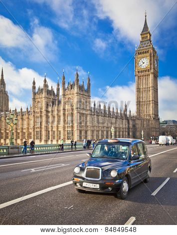 LONDON - Dec 21:  A famous black cab crosses Westminster Bridge in front of Parliament on December 21st, 2012 in London, England.