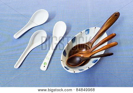 Set Of Wooden Spoon In White Bowl With Three Ceramic Spoon On Blue Background
