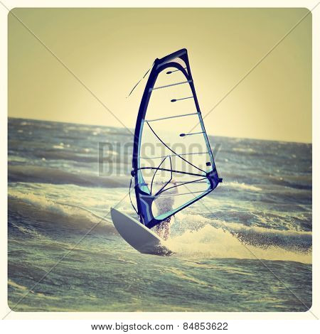 Lone anonymous windsurfer in the ocean catching a wave with Instagram effect filter