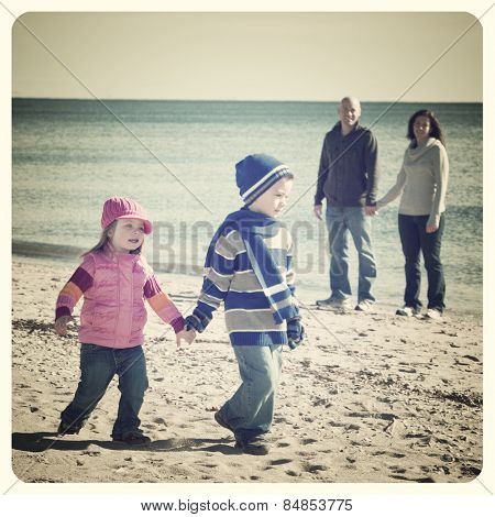 Handsome family walking at the beach with focus on little girl with Instagram effect filter