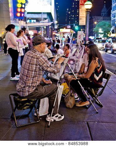 NEW YORK, USA - JUNE 28th 2014: Street artist drawing a young couple on 42nd Street in the busy theater district.