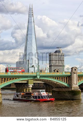 LONDON, UK - AUGUST 22, 2014: The Shard overlooking the River Thames with a red bus crossing the bridge.