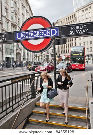 LONDON, UK - AUG 22, 2014: Two women entering the Monument Station London Underground. The London Underground sign is a famous London icon.