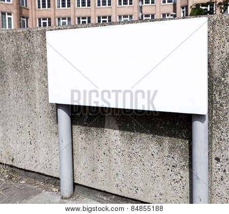 Blank street sign against a concrete wall
