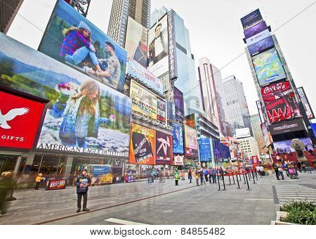 NEW YORK, USA - NOVEMBER 13th, 2014: People walking through New York's famous Times Square area with colorful signage.