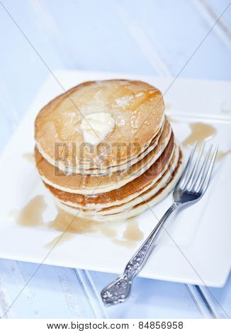 A stack of 6 cooked plain pancakes with melting butter