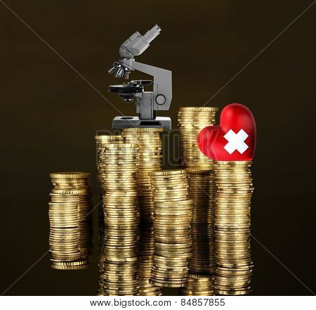 Red heart with cross sign and microscope on stack of coins on dark brown background
