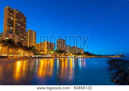 Tall Buildings On Waikiki Reflect In The Water