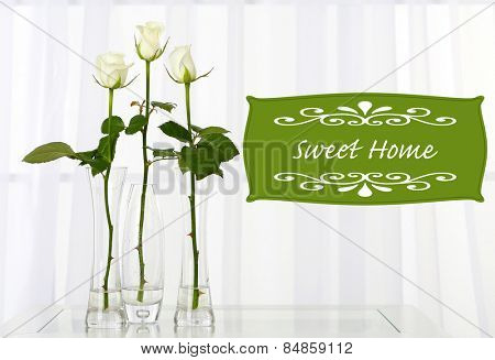 Beautiful white roses in vases on window background and space for your text