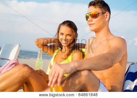 Young couple relaxing on a deck chairs on a beach