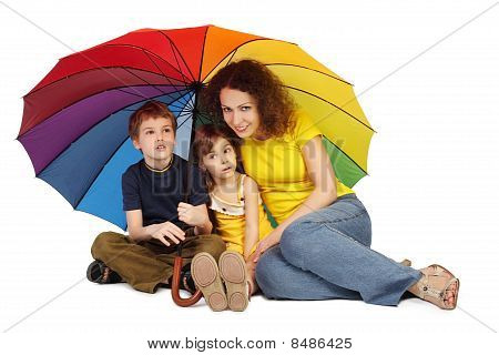 Mother, Daughter And Son With Big Multicolored Umbrella Sitting Isolated On White