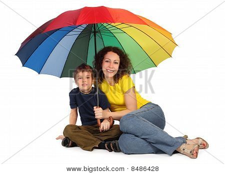 Mother And Son With Big Multicolored Umbrella Sitting Isolated On White And Looking At Camera