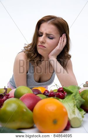 Portrait of a dissatisfied woman sitting at the table with fruits