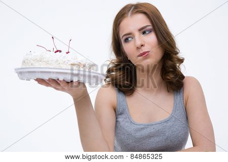 Portrait of a pensive woman looking at the cake over gray background