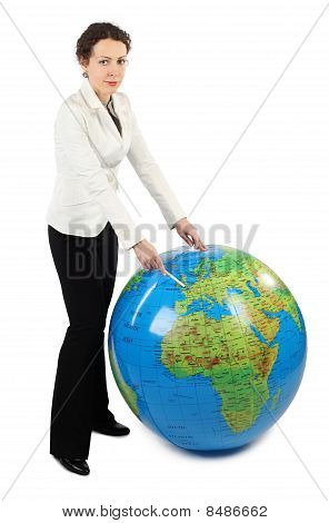 Young Woman In White Jacket Standing And Pointing At Europe On Big Inflatable Globe, Isolated