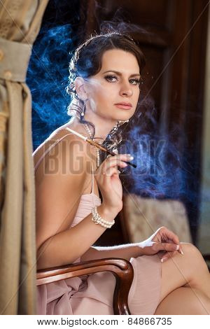 Pretty Woman Is Sitting On The Chair And Smoking Cigarette. Blue Smoke On The Background.