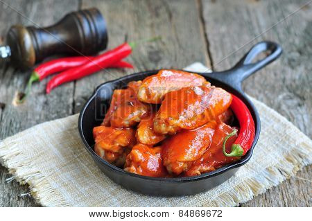Hot Chicken Wings Barbecue in Black Saucepan isolated