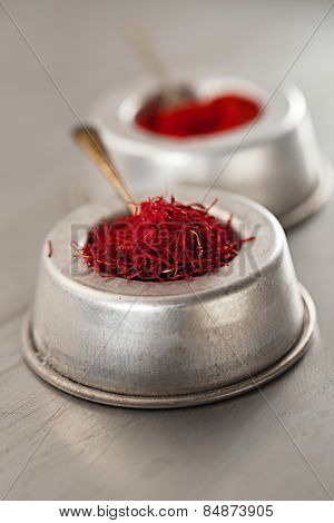 saffron spice threads and powder  in vintage  old dishes,  tin metal background, closeup