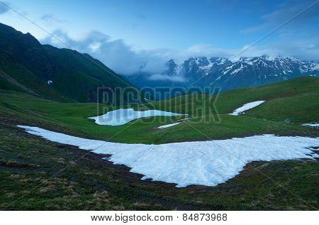 Evening landscape in spring. Mountain Lake and snowfields. lake Koruldi, main Caucasian ridge. Zemo Svaneti, Georgia
