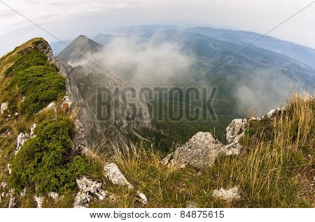 Rocks and cliffs in clouds trekking path at Suva Planina mountain