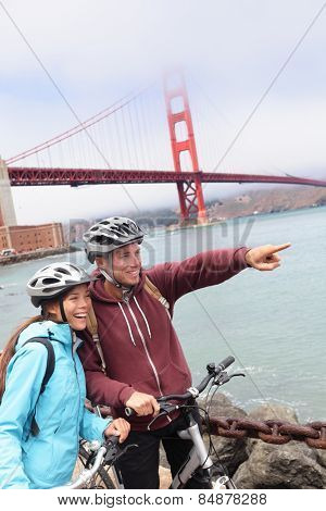 Golden gate Bridge - happy biking couple sightseeing in San Francisco, USA. Portrait of young couple tourists on bike tour enjoying the view at the famous travel landmark in California, USA.
