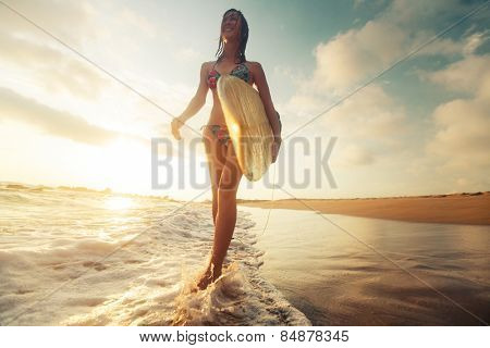 Surfer girl walking with the surf board on the beach