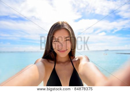 Selfie woman taking self portrait at beach. Young Asian adult holding smartphone camera to take a picture of herself during her summer vacations on a tropical beach. Suntan and bikini concept.