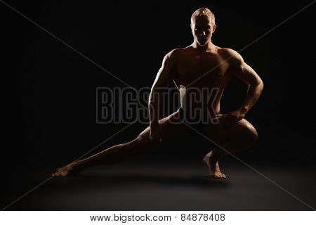 Athletic muscular man posing over black background. Men's beauty. Bodybuilding. Sports.
