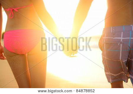 Holding hands couple in swimwear at beach. Rear view of fit couple's buttocks and legs as weight loss concept at beach sunset during summer vacations.