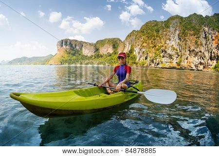 Young lady relaxing in the kayak at sunny day