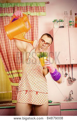 Muscular man in an apron watering the flowers with expression. He is in the pink kitchen. Family, love concept. Valentine's day. Women's day.