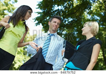 Business people having a discussing outdoor. Smiling, happy, standing gesturing, jacket and file folder in hand. Low angle view.