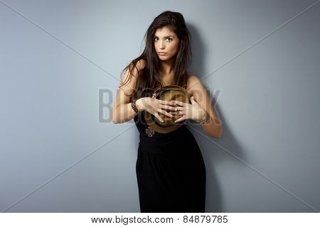 Sensual woman posing over grey wall, holding straw hat over herself.