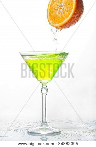 Cocktail Splash In Glass Isolated With An Orange On A White Background
