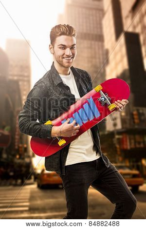 Studio portrait of a young man posing with a skateboard on street of New York