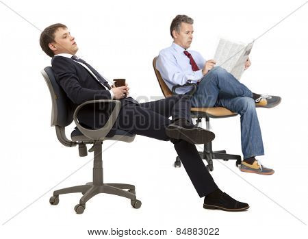Two businessman resting in armchair with legs up isolated on white background
