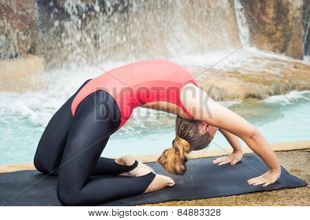 Woman practicing yoga near waterfall. Extended Camel Pose. Utthita Ustrasana