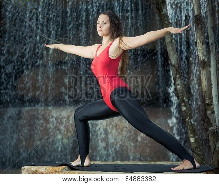Woman practicing yoga near waterfall. Warrior Pose.Virabhadrasana