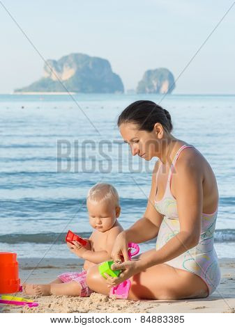 Baby and mom are playing beach toys