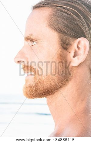 Profile portrait of the face of an attractive bearded man staring straight ahead with a quiet smile, close up view over a beach background with bright sunlight