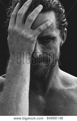 Monochrome greyscale portrait of a handsome bearded man holding his head in remorse or regret with a rueful smile