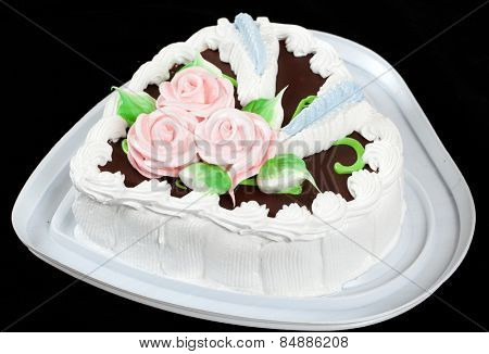 Cake with roses in heart shape on black background.