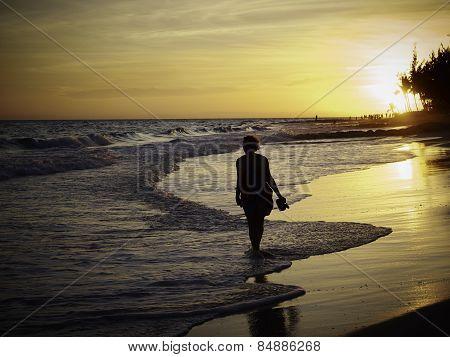 Woman Walking Along Tropical Beach At Sunset