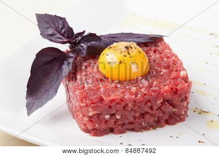 tartar of beef with egg yolk, pepper, capers and onions on a white plate