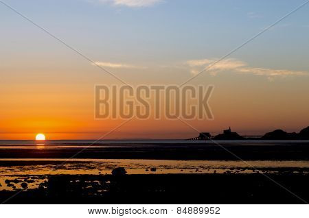 The sun rises out of the sea next to the lighthouse and lifeboat sheds in Mumbles, South Wales, casting a bright reflection on the wet sand and pools left by the receding tide