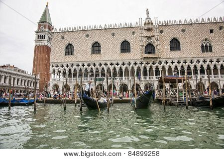 Gondolas And Gondolier With Tourists  Near Doges Palace In Summer Venice