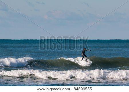 Surfer Black Wetsuit Riding The Wave