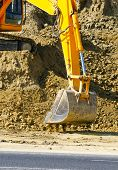picture of earth-mover  - Earth mover working on road construction and digging surface - JPG