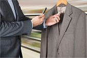 stock photo of boutique  - Man Shopping In Boutique Comparing Prices With Mobile Phone Scanning The Price Tag - JPG